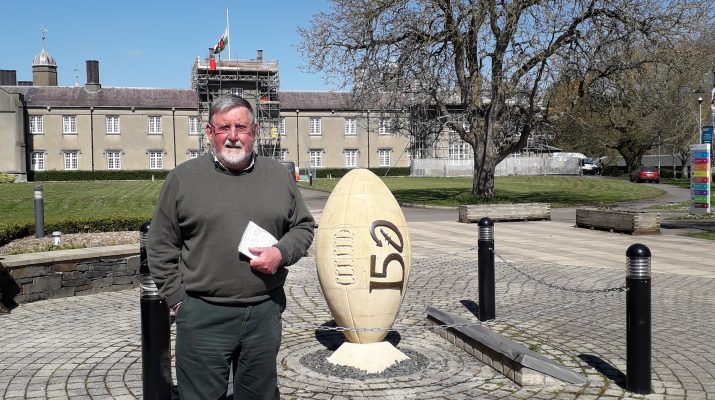 Rugby reporter Huw S Thomas beside the memorial at Lampeter College to commemorate the founding of the game in Wales in 1866